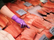 person pointing at fish meat during daytime