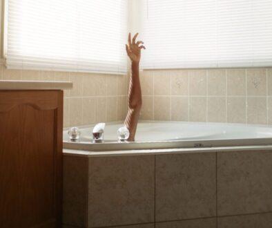 woman in bathtub near window blinds
