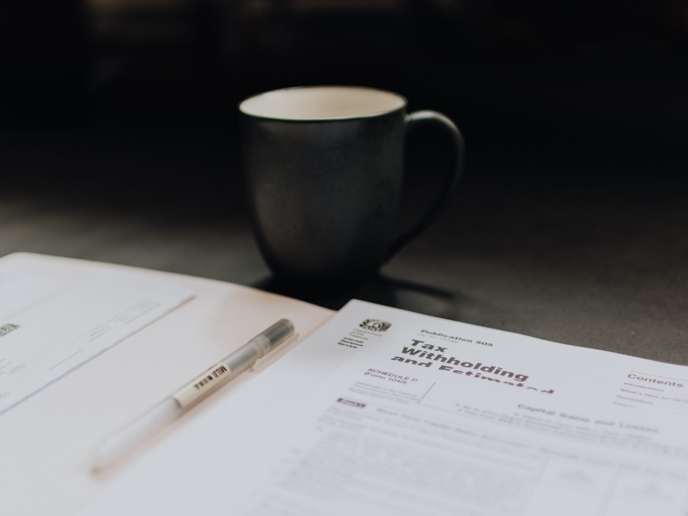 coffee mug near open folder with tax withholding paper