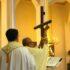 priest holding crucifix inside church