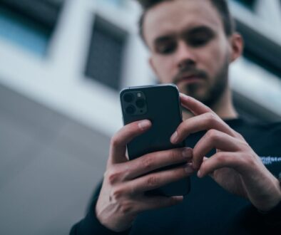 man wearing black sweater using smartphone