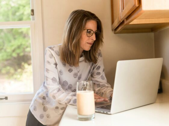 woman using her MacBook Pro inside white room