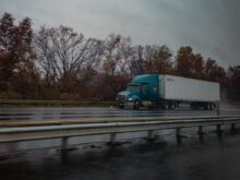 blue truck on road near bare trees during daytime