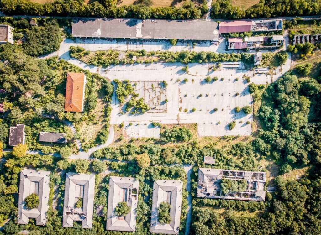 aerial photography of brown gray concrete buildings surrounded by trees
