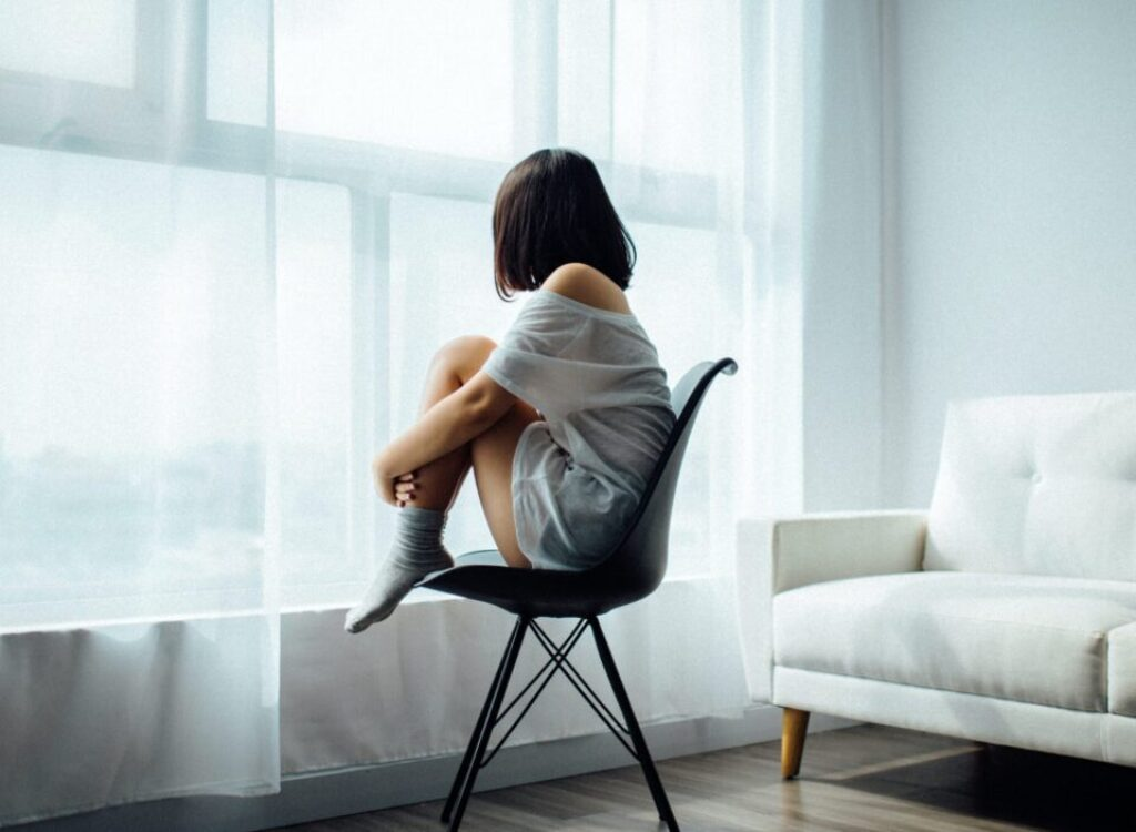 woman sitting on black chair in front of glass-panel window with white curtains