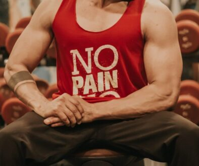 man in red tank top and black pants sitting on bench