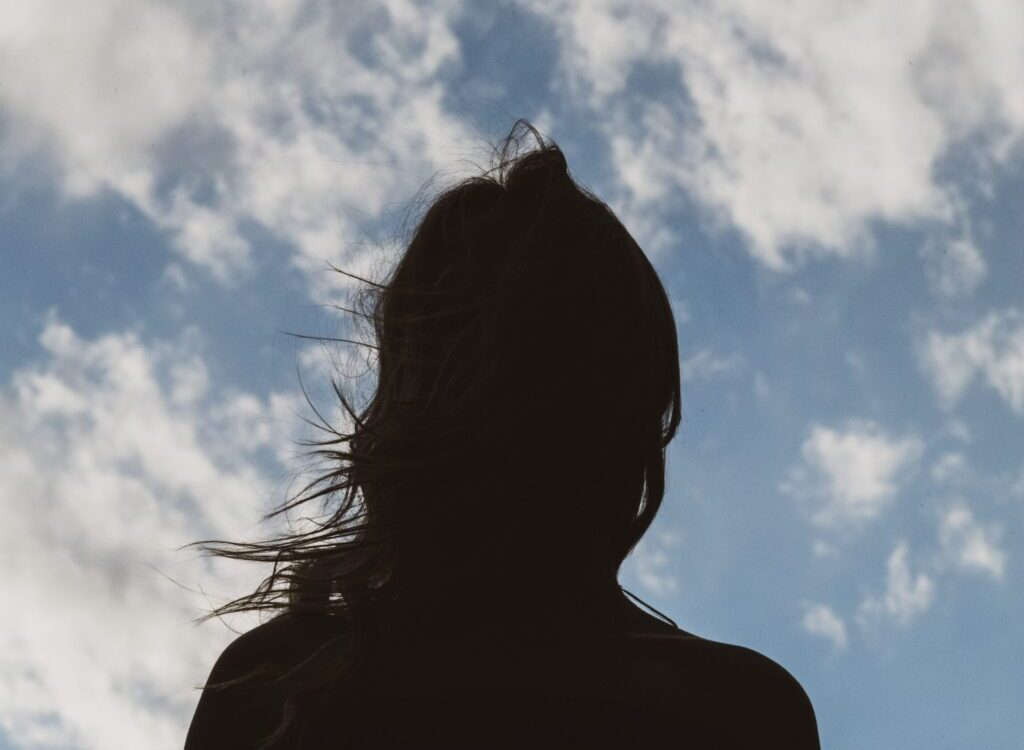 silhouette of woman under blue sky and white clouds during daytime