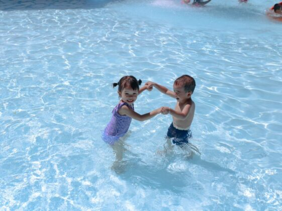 girl and boy playing in swimming pool during daytime