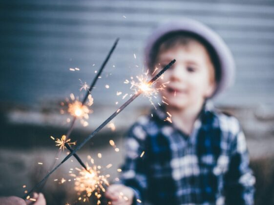 closeup photo of boy wearing blue and white plaid sport shirt holding firework