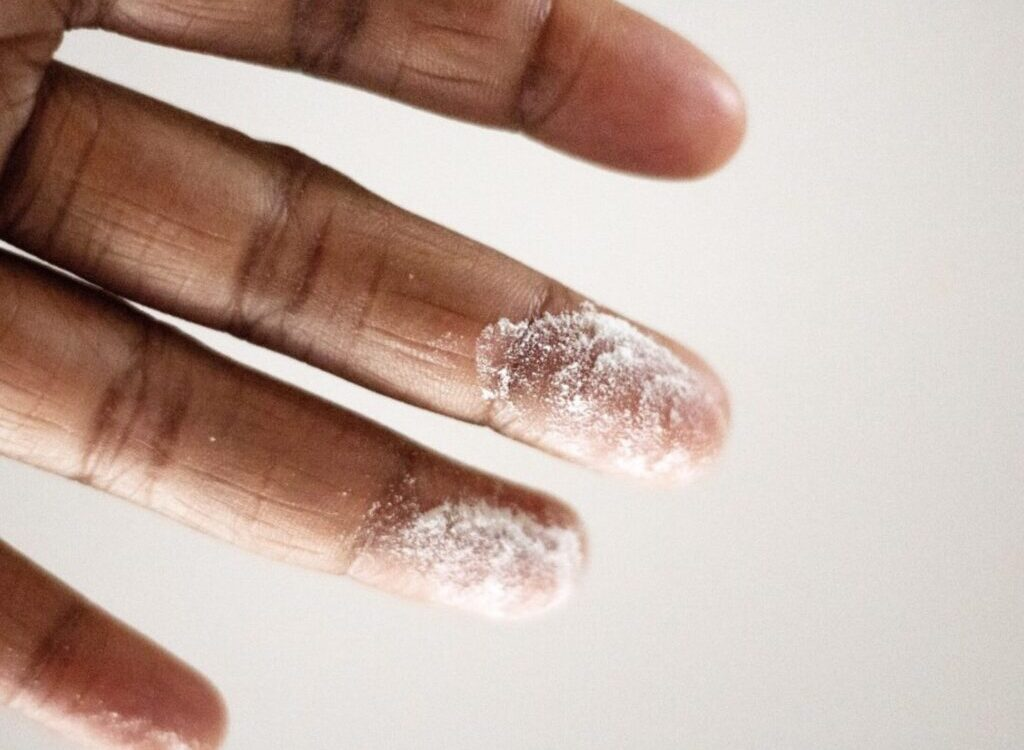 close-up photo of person's finger with white powder